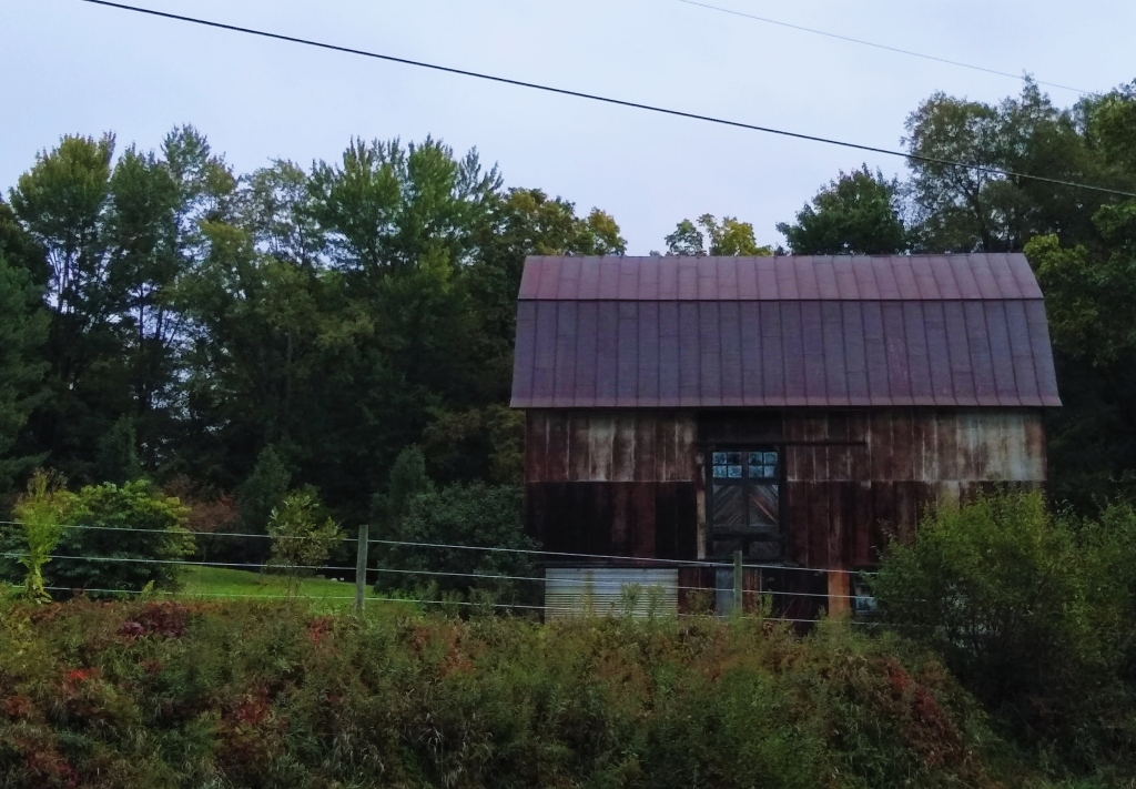A rusted old metal sided barn at the side of the road.